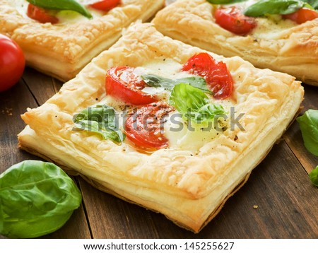 Puff-pizzas with mozzarella cheese, cherry tomatoes and baby basil. Shallow dof. - stock photo