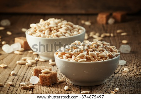 puffed sweet rice in caramel in white porcelain bowls with cane sugar and candy on an old wooden table, selective focus - stock photo