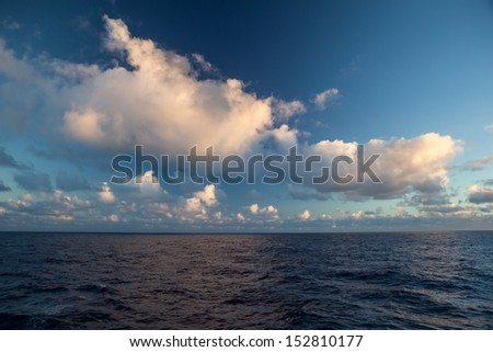 Puffy, white clouds drift over the tropical South Pacific Ocean. - stock photo