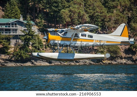 PUGET SOUND, WASHINGTON - AUGUST 4, 2014: A commercial seaplane lands at Orcas Island in Puget Sound. - stock photo