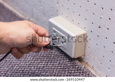 Pull out the plug from the wall socket - stock photo