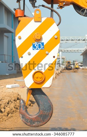 Pulley  crane on a construction site, capable of lifting 30 tons of load. Heavy duty machinery for heavy construction industry. - stock photo