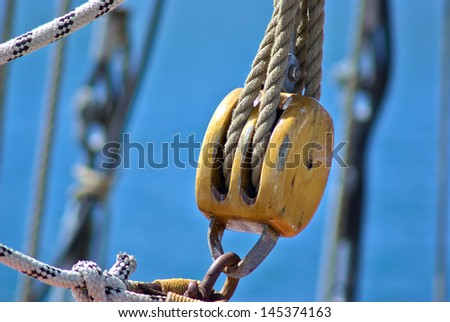 Pulley for sails and ropes made from wood on an old sail boat - stock photo