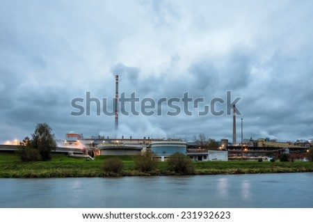 Pulp mill on the banks of the river.  Image pulp mill for the production of paper, smoke from the chimneys. Paper production harms the environment, emission of harmful substances into the air. - stock photo