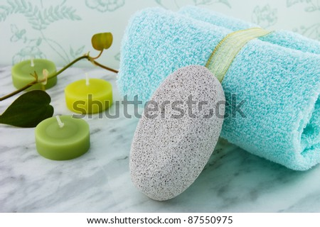 Pumice stone, white bar of soap and a rolled hand towel. - stock photo