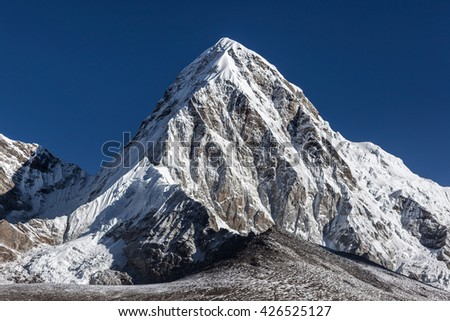 Pumori mountain summit on the famous Everest Base Camp trek in Himalayas, Nepal. Snowy mountain summit on a bright sunny day with clear sky. Beautiful mountain summit landscape in Himalayas. - stock photo