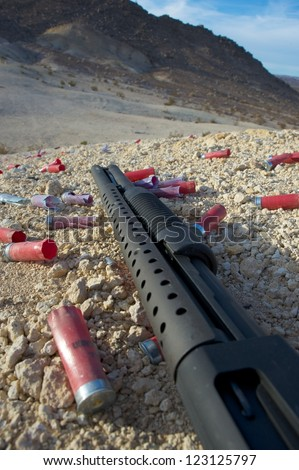 pump-action shotgun on ground surrounded by empty cartridges - stock photo