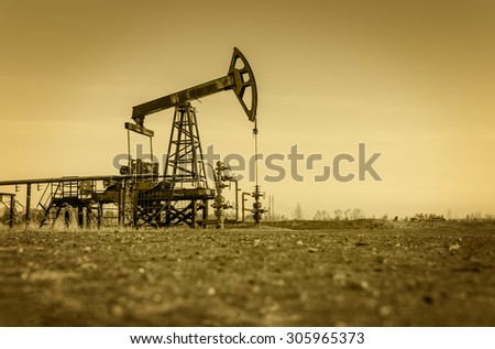 Pump jack and wellheads. Extraction of oil. Toned. - stock photo