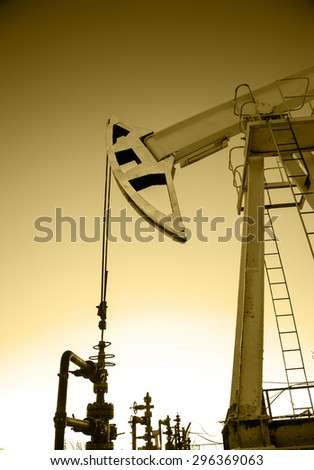 Pump jack and wellheads. Extraction of oil. Toned sepia. - stock photo