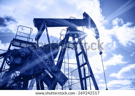 Pump jack on a sky and sun background. Extraction of oil. Toned blue. - stock photo