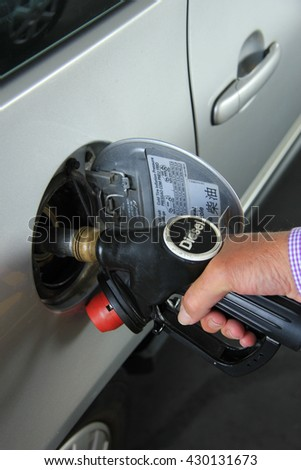 Pumping gas at a self service gas station (Diesel is a type of gas in Europe) - stock photo