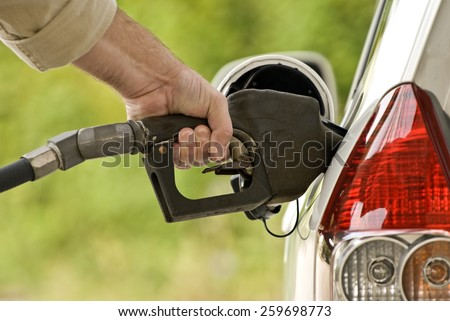 Pumping Gas At Gas Pump/ Close up of man pumping gas in car - stock photo