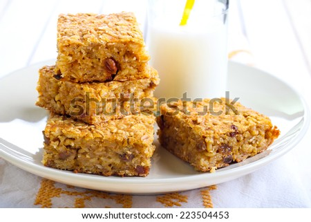 Pumpkin and oat bars with raisin and bottle of milk, selective focus - stock photo