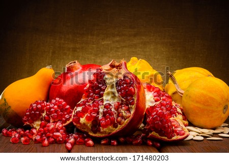 pumpkin and pomegranate on fabric background - stock photo