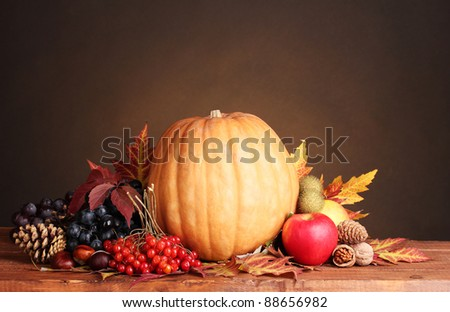 pumpkin, apples,berries and leaves on wooden table on brown background - stock photo