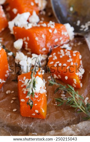 Pumpkin baked with cheese and thyme and sesame seeds. - stock photo