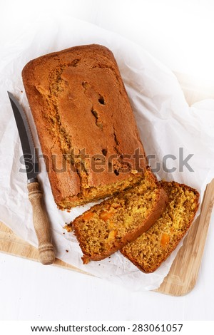 Pumpkin bread loaf and vintage knife over white wooden background. Top view - stock photo