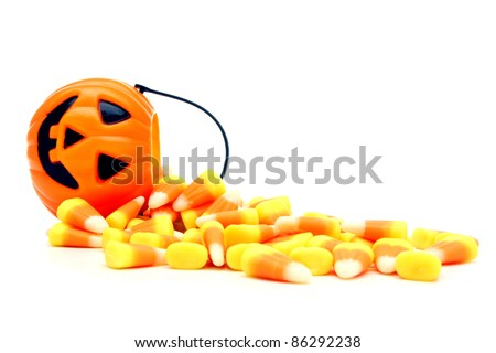 Pumpkin candy holder with spilling Halloween candy corn over white - stock photo