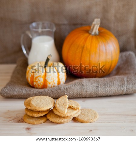 Pumpkin cookies on wooden table with pumpkins on a background, selective focus - stock photo