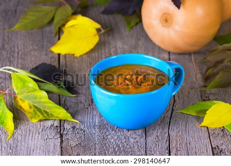 pumpkin cream soup in a blue cup on a wooden background with autumn leaves - stock photo