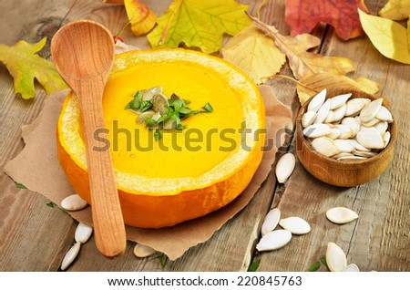 Pumpkin cream soup, seeds and dry autumn leaves on rustic wooden table - stock photo