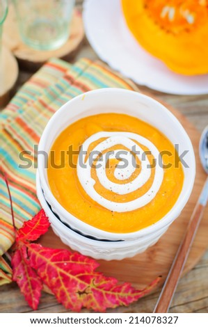 Pumpkin Cream Soup with Sour Cream in a White Bowl, copy space for your text, shallow dof - stock photo