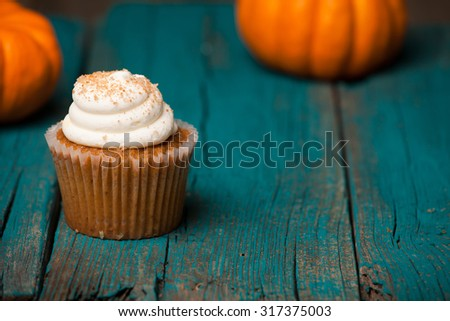 Pumpkin cupcake on blue background with mini pumpkin - stock photo