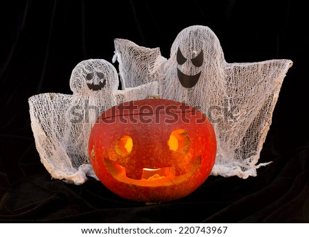 Pumpkin head with ghosts in the darkness - stock photo
