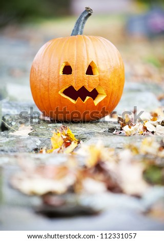 Pumpkin on a wall with autumn leaves - stock photo