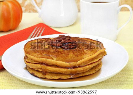 Pumpkin pancakes with pecans and syrup. - stock photo