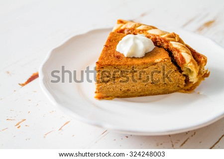 Pumpkin pie and decorations, white wood background, closeup - stock photo