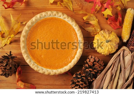 Pumpkin pie shot from a high angle with autumn decorations - stock photo