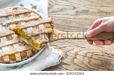 Pumpkin pie with hand taking a slice - stock photo