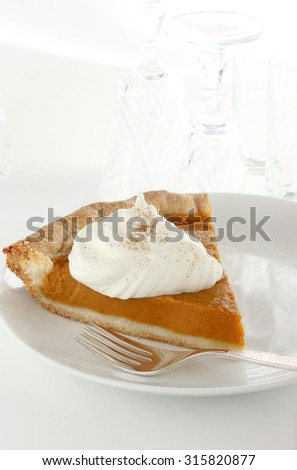 Pumpkin pie with over sized spoonful of whipped cream and a hint of cinnamon - stock photo