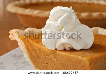 Pumpkin pie with swirls of whipped cream on decorative plate.  Whole pie in soft focus in background.  Macro with shallow dof. - stock photo