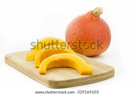 Pumpkin pieces on a wooden board, isolated - stock photo