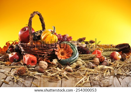 pumpkin, pomegranate, apple, nuts, berries and grain with basket on old weathered wooden floor - stock photo