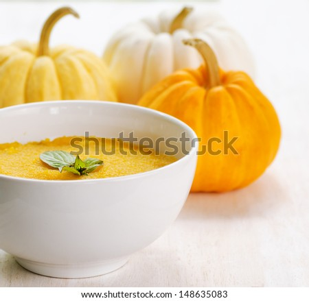 Pumpkin porridge and pumpkins on white wooden table. - stock photo