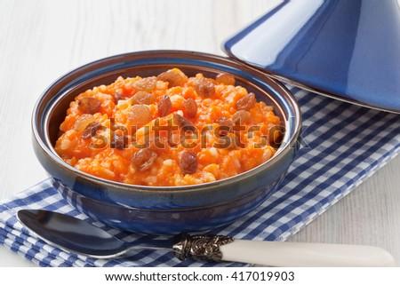 Pumpkin risotto with raisins in tajine pot on wooden background/Pumpkin risotto with raisins  - stock photo