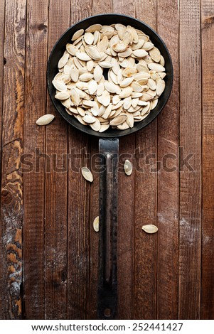 Pumpkin seeds in a pan on the wooden table - stock photo