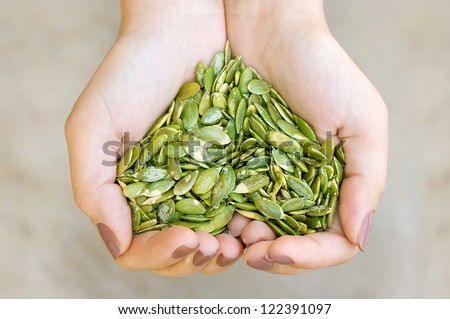 Pumpkin seeds' kernel in woman hands forming heart shape - stock photo