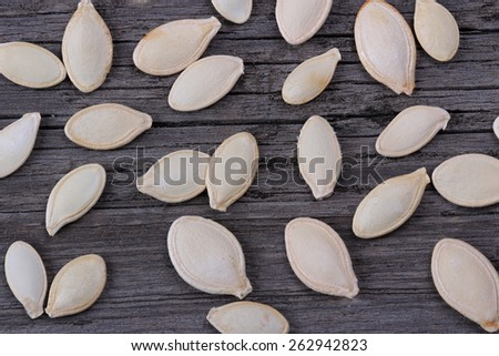 Pumpkin seeds on old wood background - stock photo