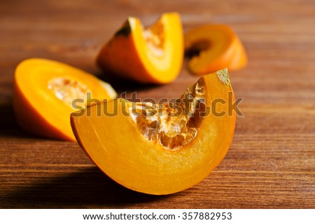 Pumpkin slices with seeds on a wooden background. Selective focus. - stock photo