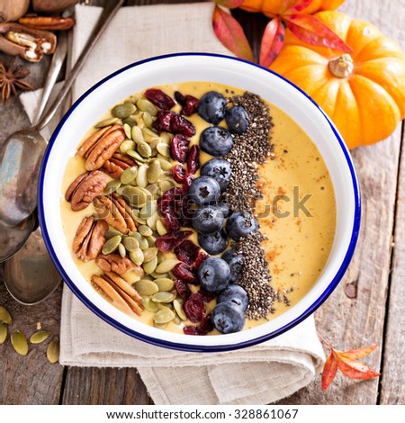 Pumpkin smoothie bowl with chia seeds, pecans, cranberries and blueberries - stock photo