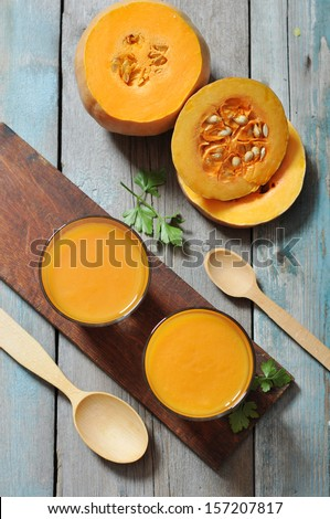 Pumpkin smoothie in glass on rustic wooden background - stock photo