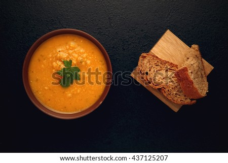 Pumpkin soup, bread and green on the wooden board. Delicious, vegetarian meal. Top view. Close-up with copy space. Toned image. - stock photo
