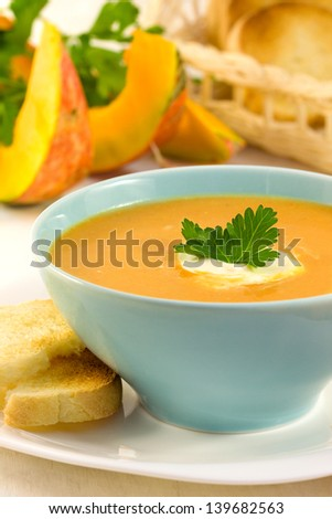 pumpkin soup in a blue bowl on a wooden board - stock photo