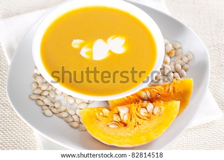 Pumpkin soup in a bowl and two pieces of pumpkin - stock photo