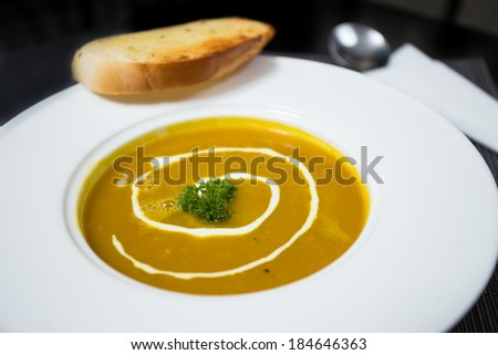 Pumpkin soup in white dish with sliced bread - stock photo