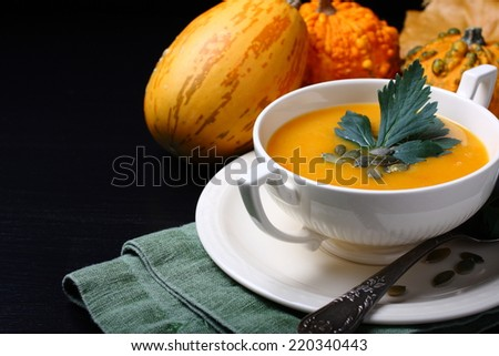 Pumpkin soup in white plate with celery leaves  on black background - stock photo
